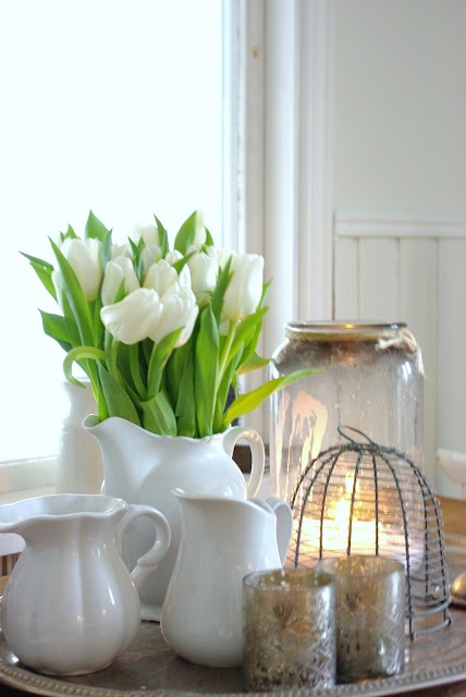 a white jug with white tulips and candles is a stylish vintage inspried combo for spring or Easter