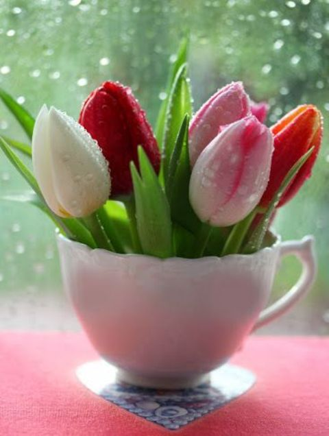 a vintage teacup with various bright tulips is a cool sprign or Easter decoration for your kitchen or any other space