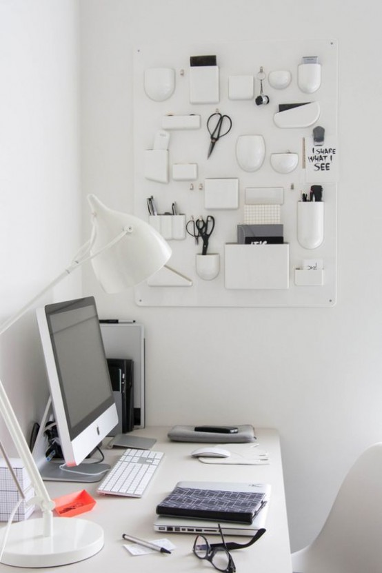 a creative white wall-mounted organizer with various vases, holders and holding units for all the office stuff