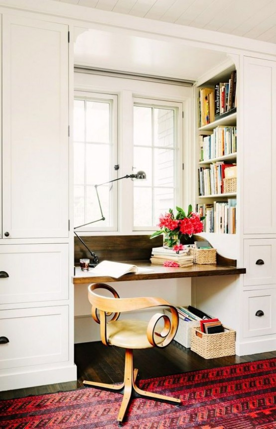 built-in shelving in the sides of the bookshelves are a nice idea to squeeze some storage space into a tiny nook