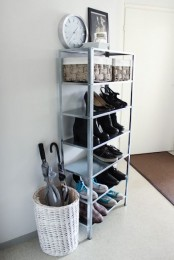 use an IKEA Hyllis shelf to store shoes and boots, boxes for storage and a clock on top the shelf