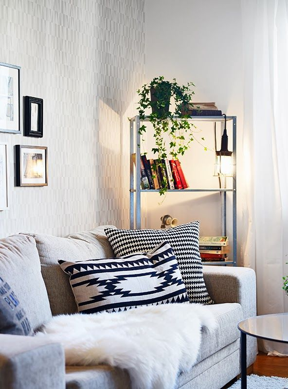 an IKEA Hyllis shelving unit with books, greenery and hanging lights is a very comfrotable storage unit