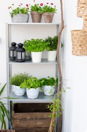 an IKEA Hyllis shelf used as an outdoor garden with potted greenery and blooms and some lanterns
