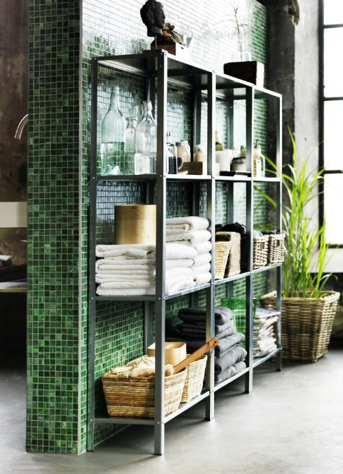 Hyllis shelves in a bathroom for storing towels, baskets with bathroom stuff, glasses, bottles and candles