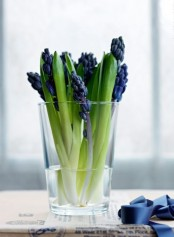 a sheer glass with purple hyacinths is a pretty and very fast and easy decoration for your space