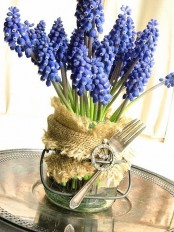 a jar with burlap, a fork with a brooch and bright purple hyacinths for a rustic and farmhouse spring centerpiece
