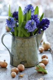 a rust metal jug with bold purple blooms and greenery for a rustic spring touch to your decor