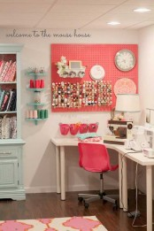 a coral pegboard with containers and hanging units with paint