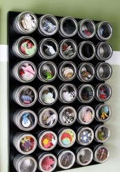 a magnetic board with cans with sheer lids for storing small stuff