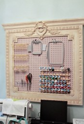 a blush pegboard in a vintage frame with wire baskets, frames and ledges