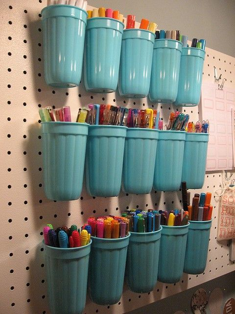 a pegboard with turquoise plastic holders is ideal for storign markers and pencils