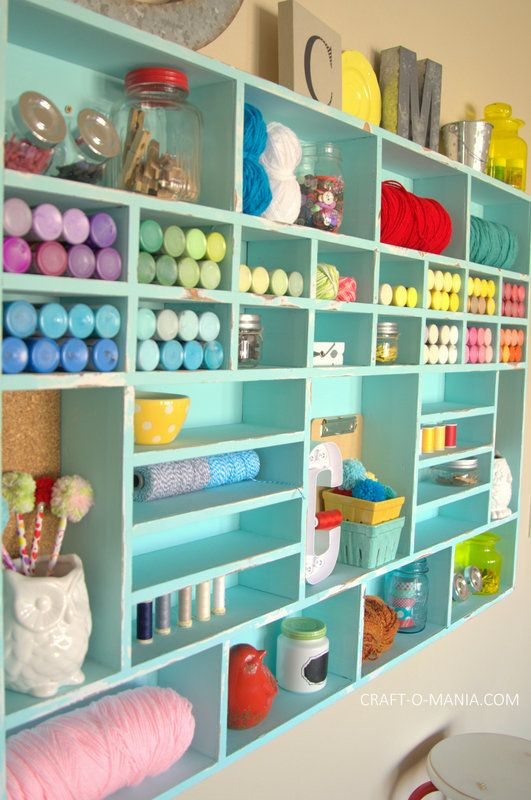 a turquoise open storage unit with lots of small shelves inside