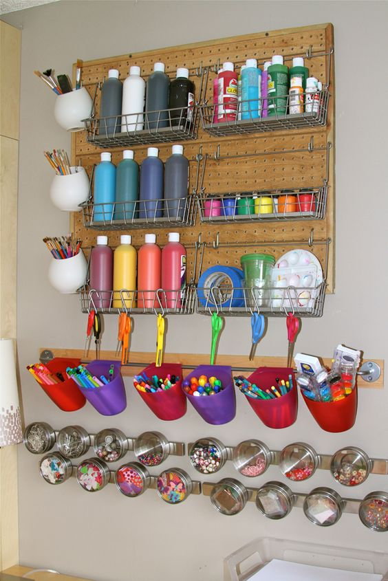 a pegboard with lots of hanging units, wire baskets and colorful plastic buckets