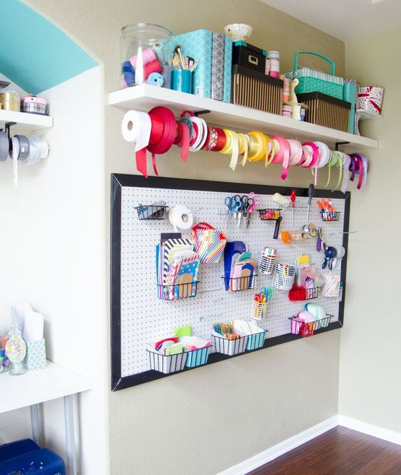 a pegboard with containers and wire baskets and an open shelf with boxes