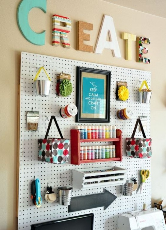 a pegboard with lots of shelves, ledges, buckets and even hanging bags
