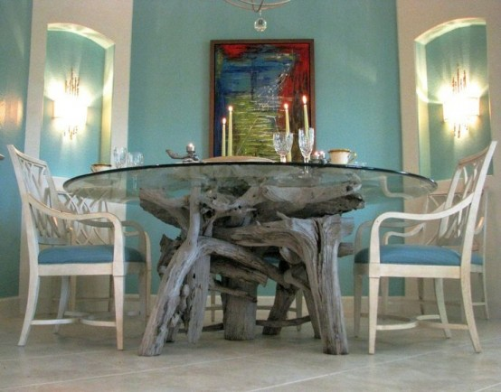 a dining table made of a glass tabletop and a driftwood base for a coastal feel