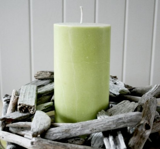a green candle in a driftwood candle holder is a cool rustic and beachy idea