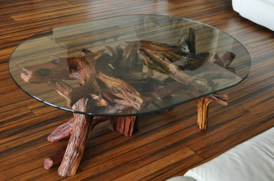 a large coffee table with a driftwood base and a glass tabletop