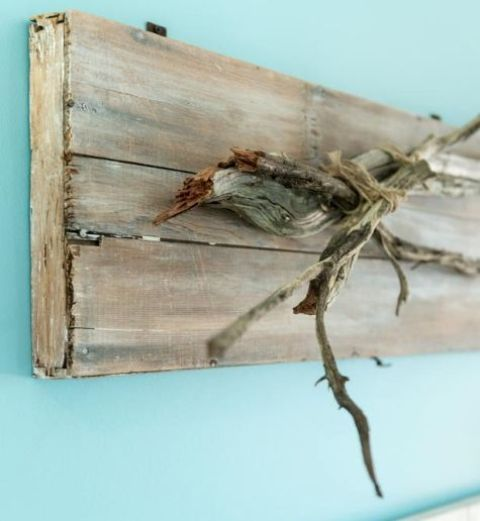 a wooden piece with driftwood attached as a clothes or jewelry hanger or an artwork