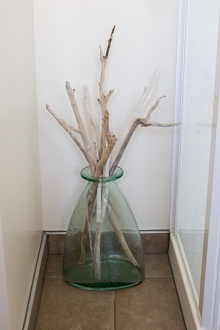 a large glass vase with branches is a cool idea to decorate your home