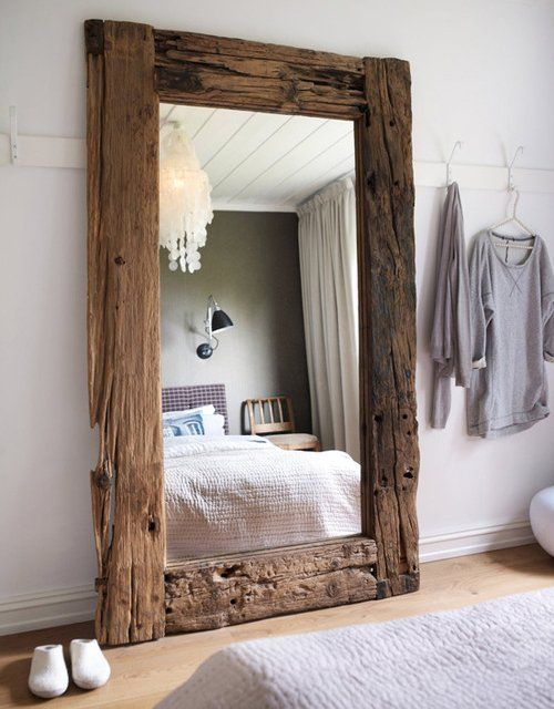 an oversized mirror in a driftwood frame is a stylish idea with practical value for a bedroom