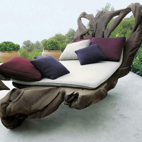 an oversized driftwood furniture piece with cushions and pillows for outdoors