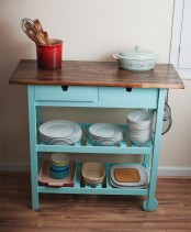 a blue Ikea Forhoja cart with a wooden countertop used in the kitchen for storage of various necessary things