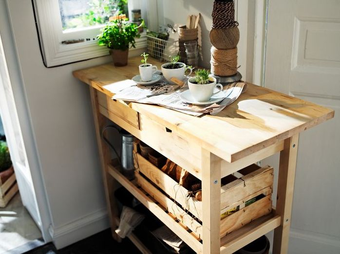 an IKEA forhoja cart used as a gardening station allows storign a lot of things and use the countertop for planting