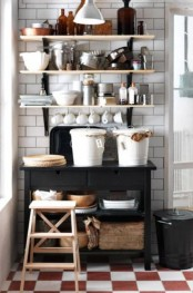 a black IKEA Forhoja cart used as kitchen furniture, it features much sotrage space and you can hang some shelves over it