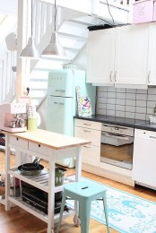 a white Ikea Forhoja cart with a wooden countertop as a kitchen island for storage and for cooking at the same time will save much space