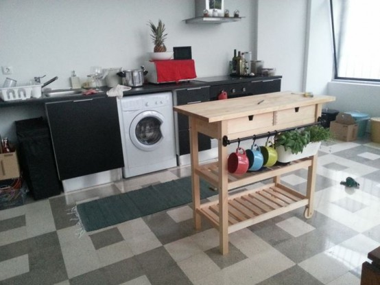 a simple wooden Forhoja cart with a metal trail for holding a planter with herbs is a nice and space-saving kitchen island