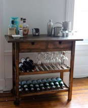a dark stained Ikea Forhoja cart used as a home bar with lots of glasses, bottles, barware and other necessary stuff