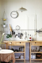 a kitchen cooking space formed by two Ikea Forhoja carts and a large and long rail for hanging various stuff