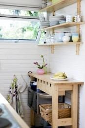 an Ikea Forhoja cart with small drawers for storage, with open storage and matching open shelves over the cart