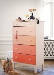 an ombre coral Tarva hack with each drawer of a different shade and white knobs for a touch of color