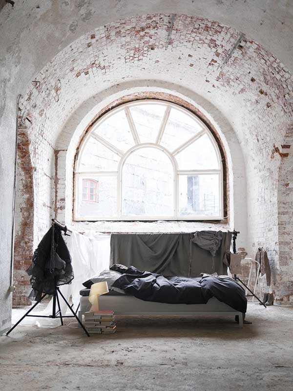 an industrial bedroom featuring whitewashed brick walls and an arched ceiling plus a concrete floor looks raw and statement
