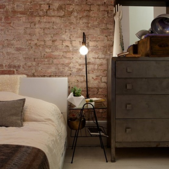 a vintage industrial bedroom is made finished off with an exposed brick wall - it's a perfect decor feature for such a space
