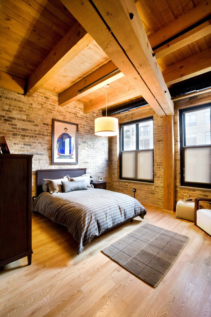 a welcoming modern bedroom with dark stained furniture, wooden beams and an exposed brick wall   both these features add interest to the space