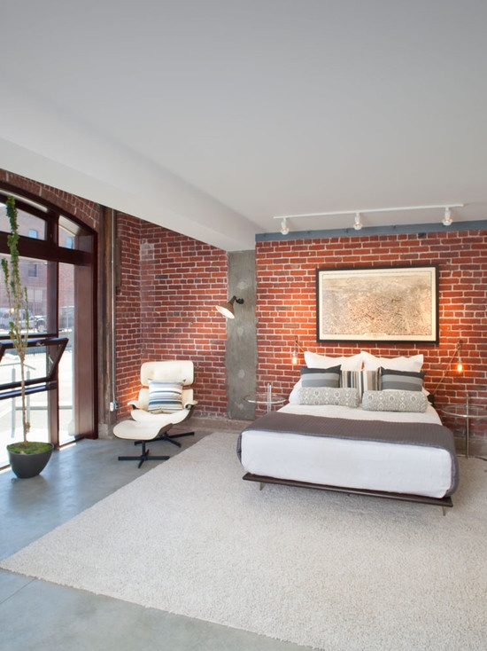 a mid-century modern bedroom with industrial touches - concrete, metal lamps and an exposed brick wall