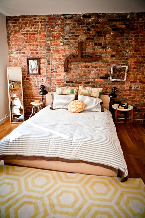 an eclectic bedroom is made catchier with an exposed brick wall that also brings a touch of color