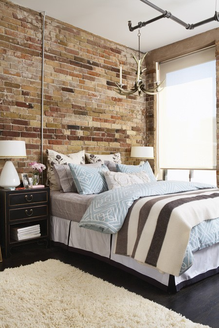 a chic bedroom with art deco touches and a fake brick wall that brings texture along with pipes and antlers