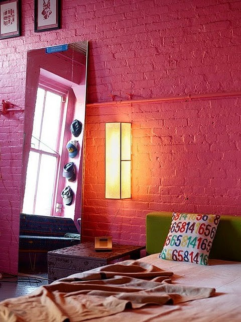 a colorful modern bedroom makes a statement with a red brick wall that takes over the whole space