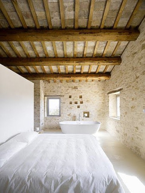 a rustic bedroom features stone and brick walls, a wooden ceiling and beams and a modern bed and tub that contrast them