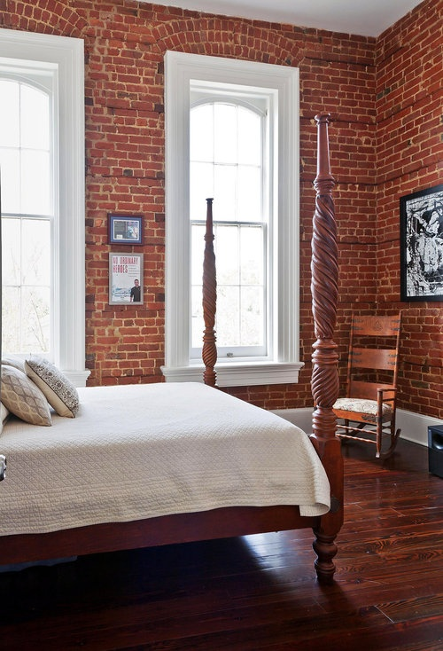 red brick walls, a redwood floor and redwood bed create an elegant bedroom in the reddish shades