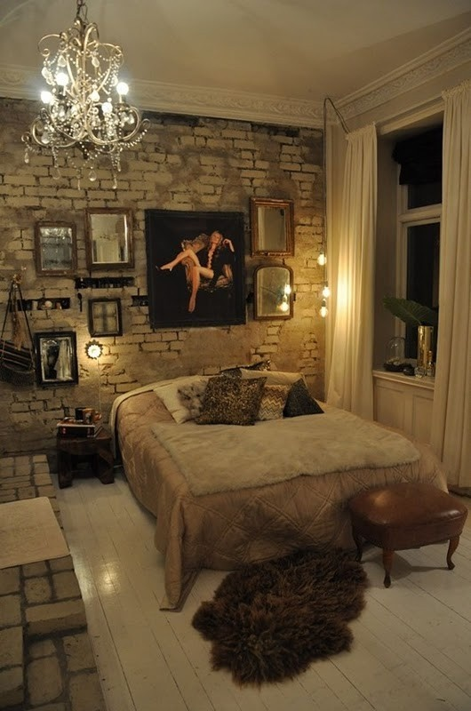 an eclectic bedroom with a white brick wall that adds a raw touch to the space and elegant artworks