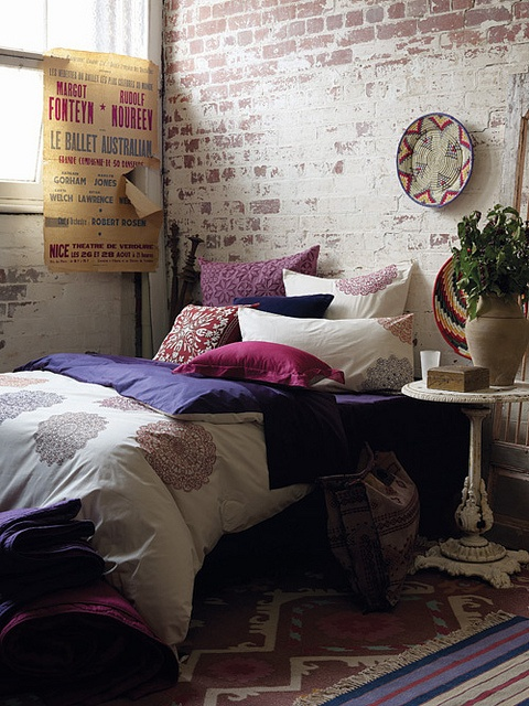 a colorful boho bedroom is made more modern and edgy with a whitewashed brick wlal