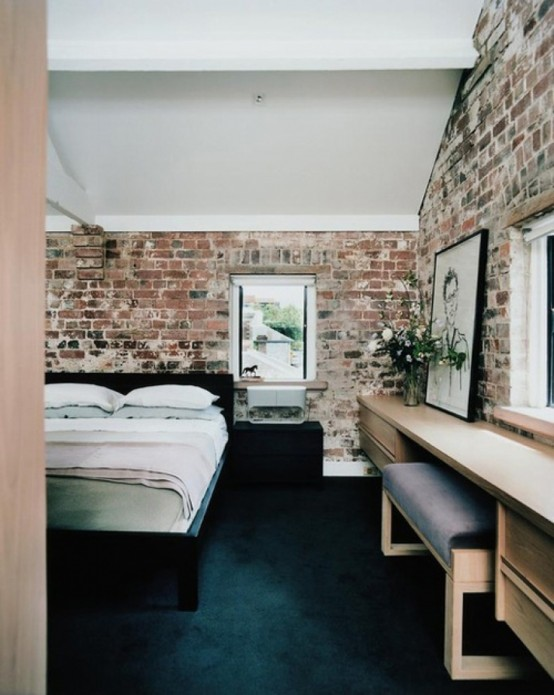 stylish contemporary bedroom is spruced up with exposed brick walls that give it a character and a unique look