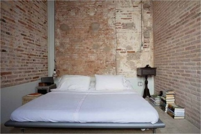 a very simple bedroom with a laconic modern bed and exposed brick walls aorund that add color, texture and interest taking over the whole space