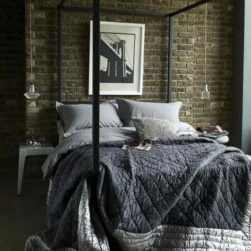 a moody bedroom with a dark brick statement wall and a black canopy bed looks very chic and welcoming