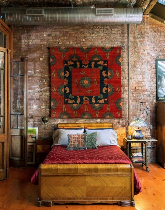 an industrial bedroom with a brick wall, an exposed pipe, metal furniture is softened with a stylish bed and a boho rug